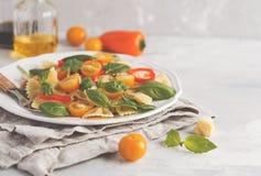 Ensalada italiana del farfalle de las pastas con las verduras, la albahaca y la espinaca Imagen de archivo