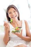 Ensalada - mujer de consumición sana que ríe comiendo la comida Foto de archivo libre de regalías