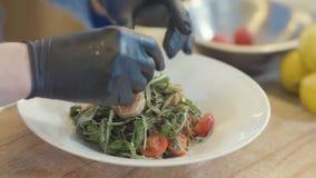 Ensalada sabrosa con arugula, los camarones del rey, el tomate y el aceite de oliva en la placa blanca grande en la tabla en la c almacen de metraje de vídeo