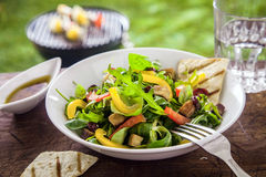 Ensalada sabrosa de la hierba en una mesa de picnic del verano Imagen de archivo libre de regalías