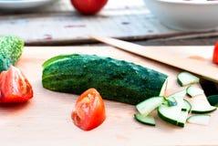 Ensalada tajada del pepino y del tomate en una tabla de cortar Foto de archivo libre de regalías