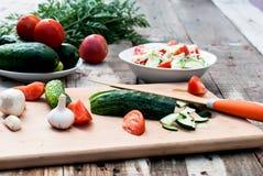 Ensalada tajada del pepino y del tomate en una tabla de cortar Fotografía de archivo