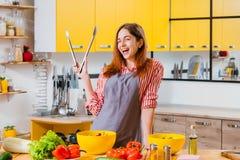 Ensalada vegetal de la señora alegre de la cocina casera de la diversión fotos de archivo