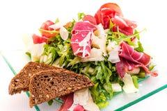 Ensalada vegetal del arugula fresco con las rebanadas del jamón, del queso y del pan en la placa de cristal en el fondo blanco, f Imágenes de archivo libres de regalías