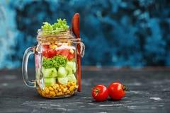 Ensalada vegetal en un tarro de cristal Tomates de la cuchara y de cereza Healt imagen de archivo