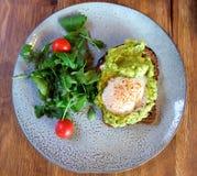 ensalada vegetal y una rebanada de pan con el huevo frito imagen de archivo
