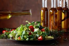Ensalada verde con el aceite de oliva que vierte de una pequeña botella Fotos de archivo