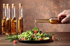 Ensalada verde con el aceite de oliva que vierte de una pequeña botella Foto de archivo