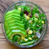 Ensalada verde con receta del aguacate La ensalada hecha en casa con el aguacate fresco, hojas de la lechuga, conservó maíz y las imagen de archivo