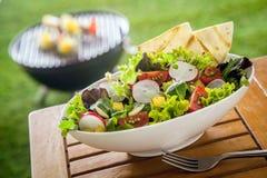 Ensalada verde frondosa fresca sana del vegano en una mesa de picnic Foto de archivo libre de regalías