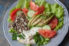Ensalada verde sana con los pescados de bacalao hervidos, lentejas, tahini, perejil, tomates Fotos de archivo