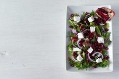 Ensalada verde sana fresca con las semillas, la cebolla y el queso feta de la granada Visión superior, espacio de la copia Imagen de archivo