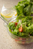 Ensalada verde, tomates y aceitunas en bol de vidrio y agua con el le Fotos de archivo