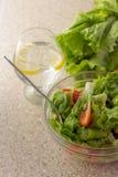 Ensalada verde, tomates y aceitunas en bol de vidrio y agua con el le Foto de archivo