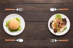 Ensalada y hamburguesa frescas en el fondo de madera foo que pone en contraste fotos de archivo libres de regalías
