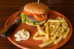 Ensalada y tomates de la hamburguesa con las patatas fritas en un earthenwa Imágenes de archivo libres de regalías