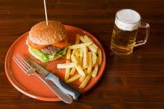 Ensalada y tomates de la hamburguesa en una placa de la loza de barro Imagen de archivo libre de regalías