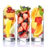 Ensaladas de fruta aisladas en blanco. Pedazos frescos de fruta en vidrios con la menta en el top. Fotografía de archivo