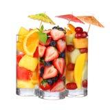 Ensaladas de fruta aisladas en blanco. Rebanadas frescas de diversas frutas en vidrio con la menta y los paraguas en el top. Imagenes de archivo