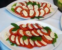 Ensaladas frescas con los tomates y el queso adornados en cuencos Fotografía de archivo libre de regalías