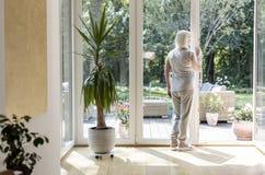 Ensam äldre kvinna i ett sjukvårdhus med trädgården under solig dag royaltyfri foto