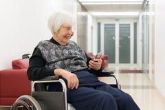 Ensam åldring 95 år sammanträde för gammal kvinna på rullstolen genom att använda den moderna mobiltelefonen arkivbild