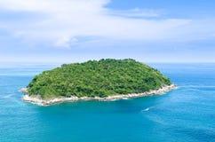 Ensam ö i ett hav och en skog Arkivbild