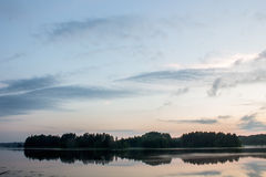 Ensam ö i mitt av sjön på solnedgången Arkivfoton