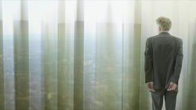 Ensam affärsman som bakom ser till och med gardiner till en cityscape stock video