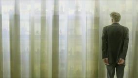 Ensam affärsman som bakom ser till och med gardiner till kontoret lager videofilmer