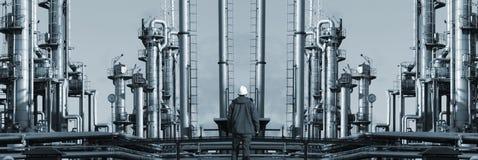 Ensam arbetare i panorama- fron av den jätte- raffinaderiet Royaltyfri Fotografi
