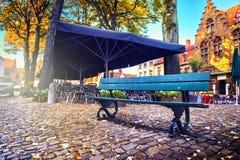Ensam bänk och utomhus- kafé i höststad Royaltyfri Fotografi
