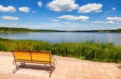 Ensam bänk vid sjön i solig dag Royaltyfria Foton