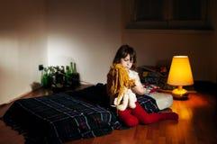 Ensam caucasian girlie i det tomma rummet som rymmer en docka royaltyfri bild