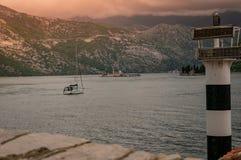 Ensam fartygsegling till fyren av oskulden av klippan i fj?rden av Kotor royaltyfri fotografi