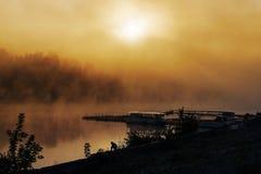 Ensam fisher på kust av floden på soluppgång med solstrålen royaltyfri fotografi