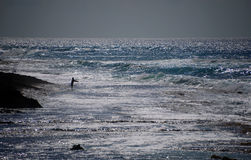 Ensam fiskare i vattnet av Oahu, Hawaii som skimrar vågor Royaltyfri Bild