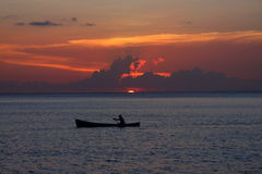 Ensam fiskare på solnedgången Arkivfoton