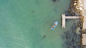 Ensam fiskebåt och träpir i turkoshavet, hav Flygbild bästa sikt Arkivfoto