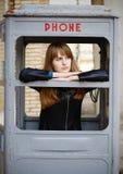 Ensam flicka i gammal phonebox royaltyfria bilder