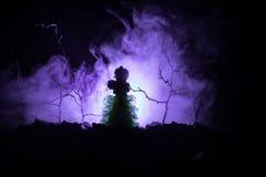 Ensam flicka med ljuset i skogen på natten eller tonad dimmig natt på begreppet för skogfasaallhelgonaafton Fotografering för Bildbyråer