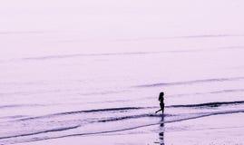 Ensam flicka på en strand Arkivbild