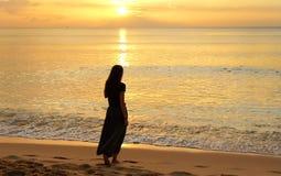 Ensam flicka som går på stranden på solnedgången Royaltyfri Fotografi