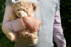 Ensam flicka som rymmer en nallebjörn som hennes bästa vän arkivfoto