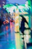 Ensam flicka under ett paraply på trottoaren bredvid en upplyst palmträd, stadsgata i regn, ljusa reflexioner arkivfoto