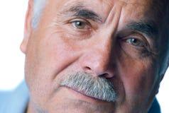 Ensam gamal man med den gråa hår och mustaschen Arkivbild