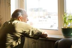 Ensam gamal man som stirrar ut ur ett fönster Royaltyfri Foto