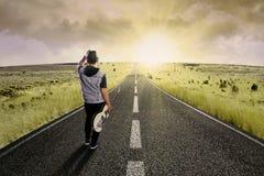 Ensam gitarrist som går på väg 2 fotografering för bildbyråer