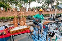 Ensam gitarrist som spelar musik på gatamässan som omges av musikinstrument arkivfoto