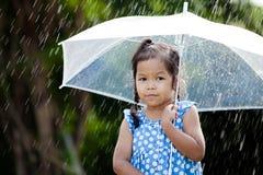Ensam gullig asiatisk liten flicka med paraplyet i regn Royaltyfria Foton